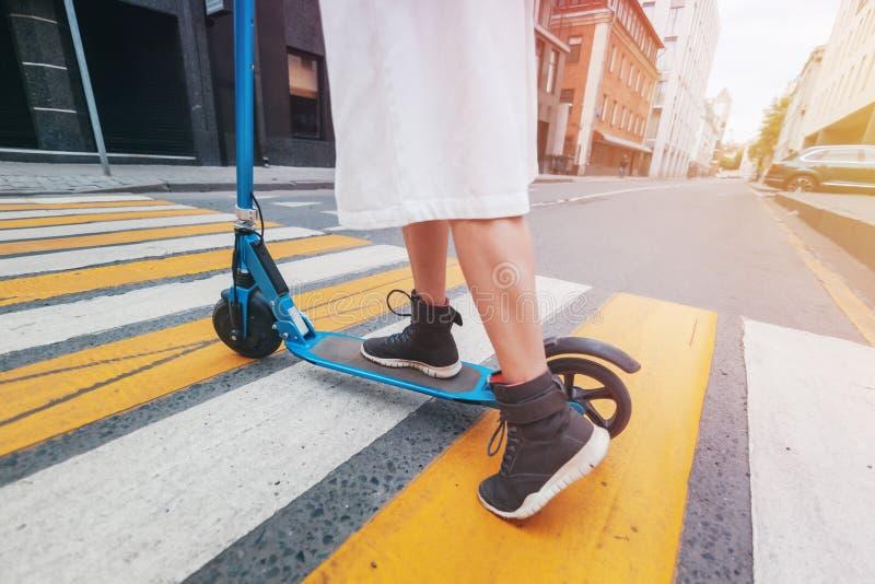La ragazza sul motorino elettrico di scossa ad un passaggio pedonale, primo piano delle gambe immagini stock
