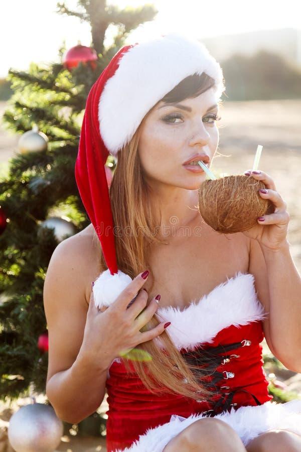 La ragazza sulla spiaggia si siede il cocktail della località di soggiorno dell'albero di Natale fotografia stock