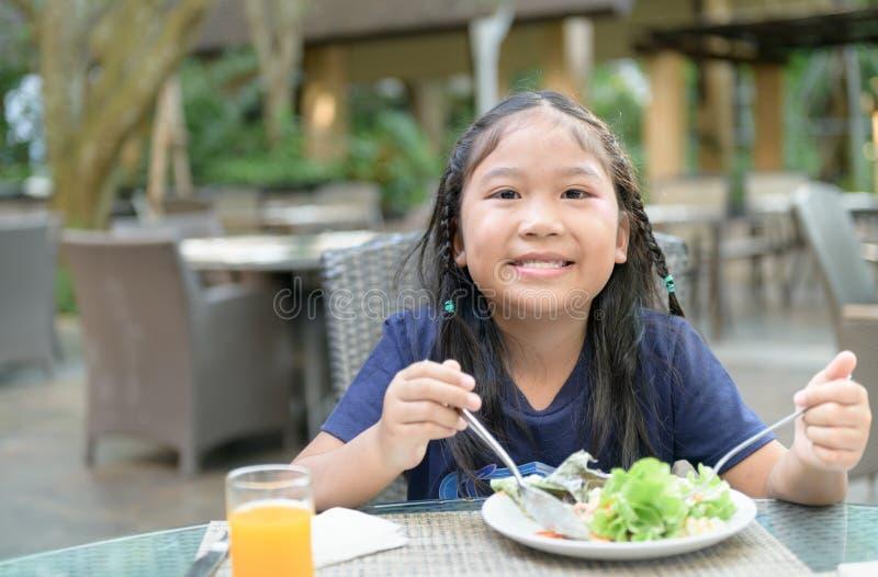 La ragazza sveglia asiatica gode di di mangiare l'insalata vegatable fotografie stock libere da diritti