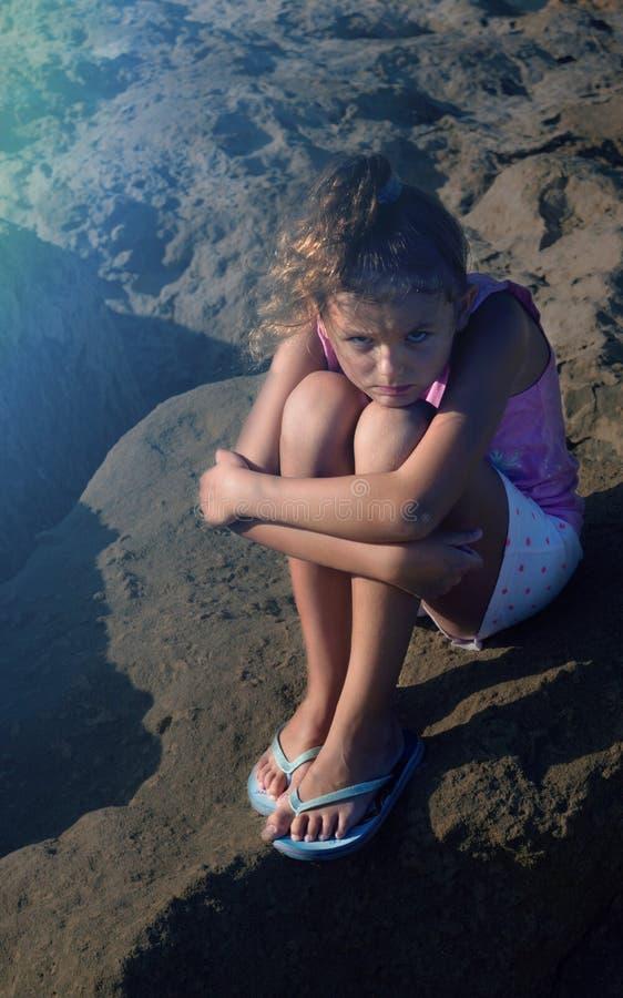 La ragazza sveglia che sembra triste, solo, spaventato, abuso, senzatetto sta sedendosi sulla terra Tempo di sera Luce solare pia immagine stock libera da diritti