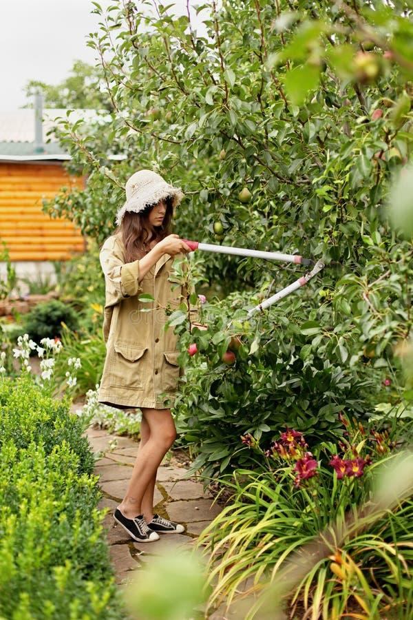 La ragazza sveglia con capelli lunghi fa il taglio con le grandi forbici del giardino fotografia stock libera da diritti