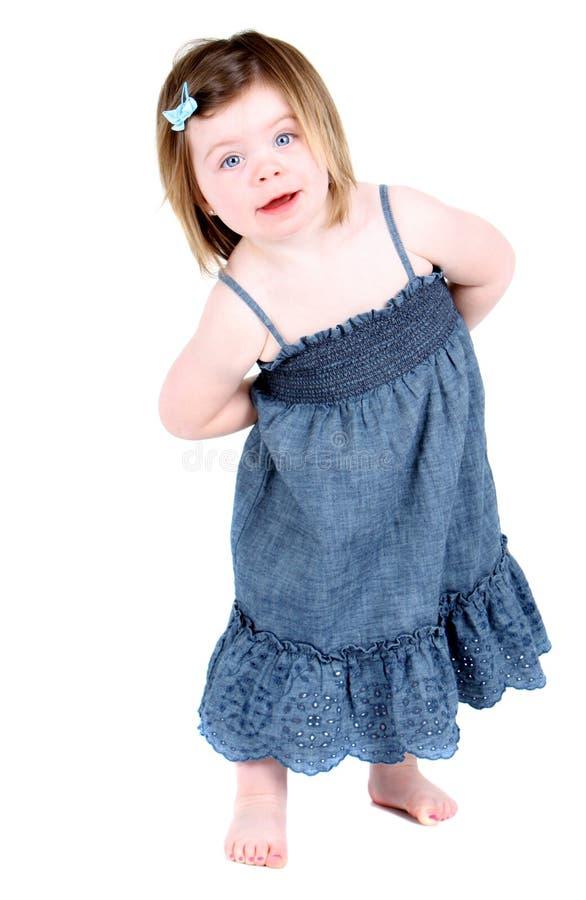 La ragazza sveglia con le braccia ha piegato dietro lei indietro immagine stock