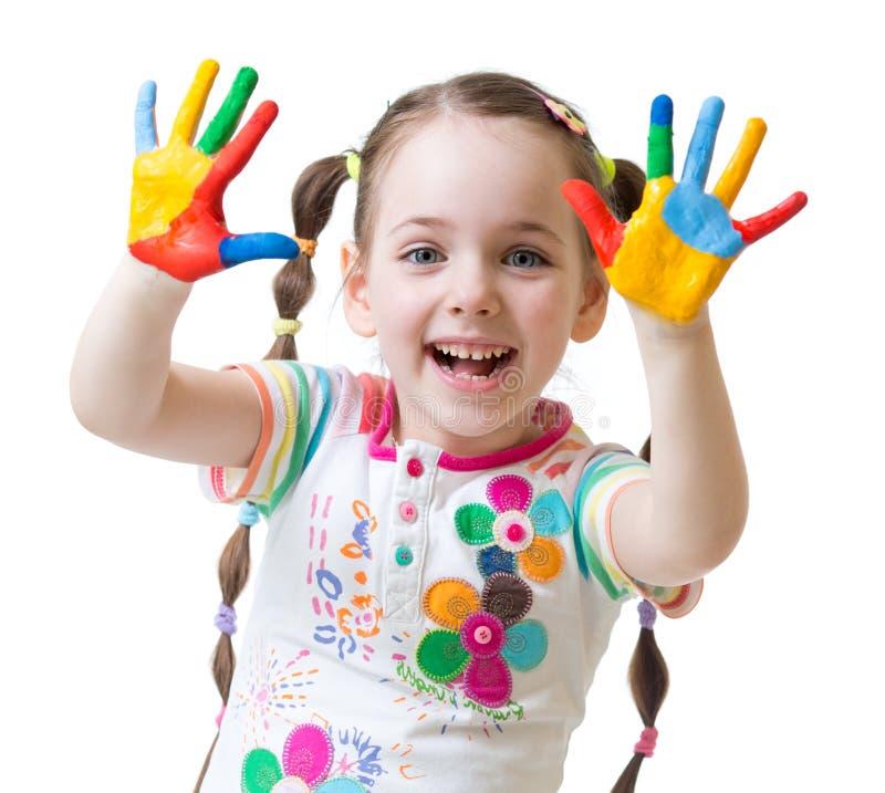 La ragazza sveglia del bambino si diverte dipingendo le sue mani fotografia stock