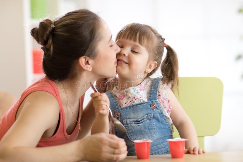 La ragazza sveglia del bambino sta avendo sano fa colazione sua madre sta baciandola con amore Il bambino sta sedendosi alla tavo fotografia stock