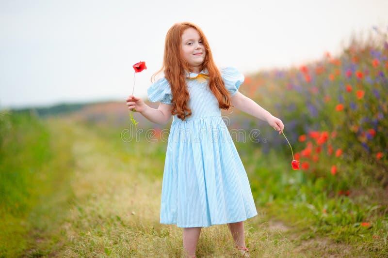 La ragazza sveglia felice del ritratto con il papavero fiorisce in sue mani fotografie stock libere da diritti
