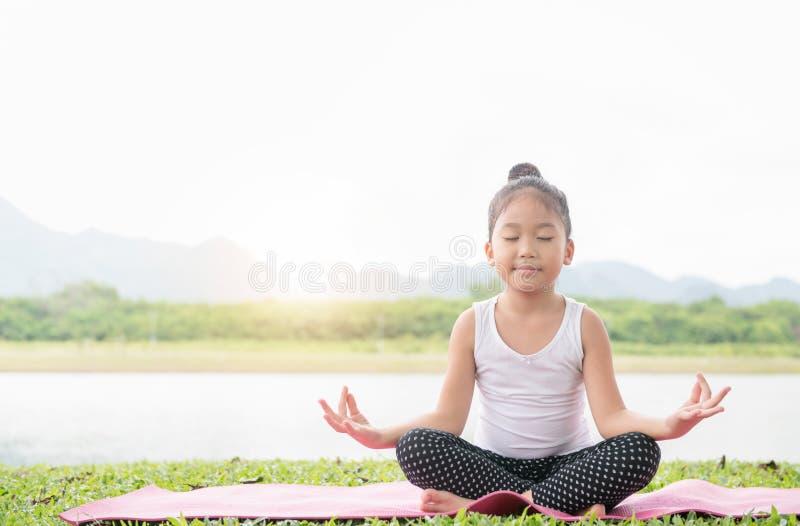 La ragazza sveglia felice pratica l'yoga e medita nel positi del loto fotografia stock libera da diritti