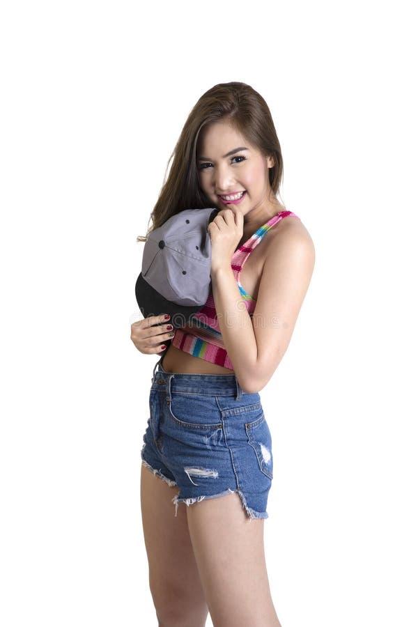 La ragazza sveglia negli shorts delle blue jeans e la maglia variopinta hanno sorriso timido fotografia stock