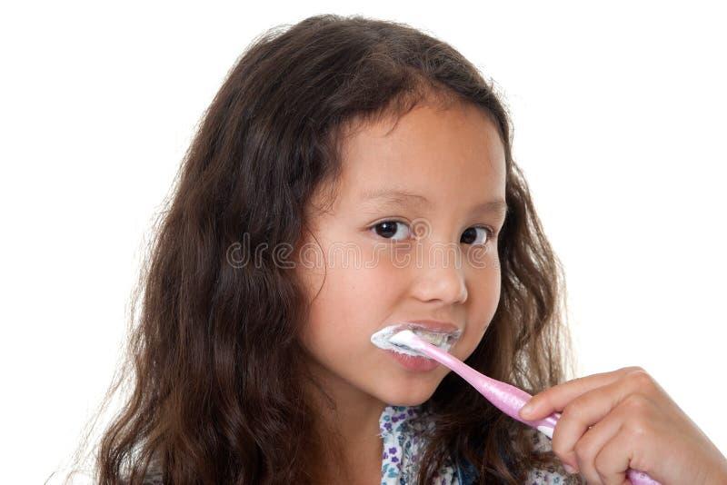 La ragazza sveglia pulisce i denti fotografia stock libera da diritti