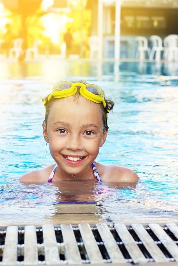 La ragazza sveglia sta sorridendo nella piscina immagini stock libere da diritti