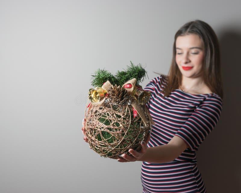 La ragazza sveglia tiene la palla fatta a mano di Natale su fondo grigio immagini stock libere da diritti