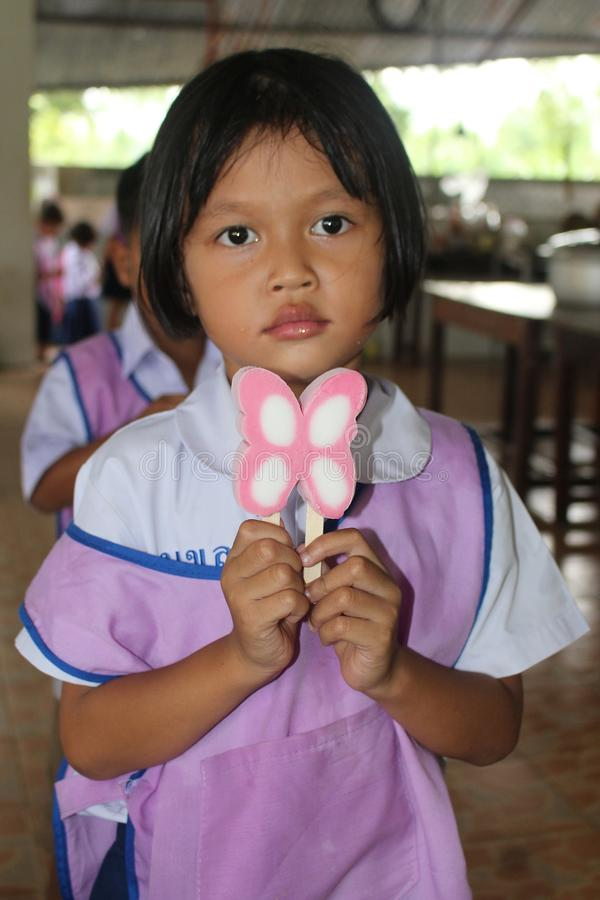 La ragazza tailandese in uniforme dello studente sta mangiando il gelato fotografia stock libera da diritti