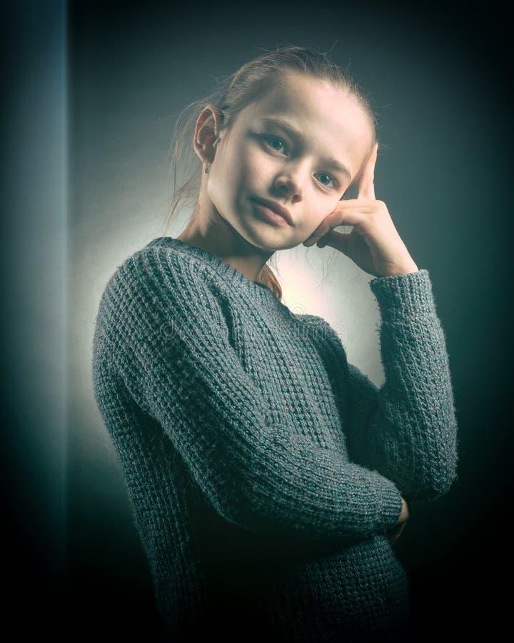 La ragazza teenager 9-12 anni, esamina la struttura, ritratto emozionale dello studio su un fondo grigio fotografia stock libera da diritti