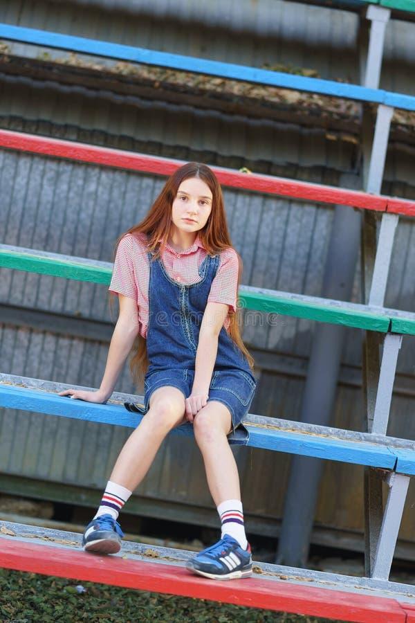 La ragazza teenager bella dai capelli lunghi di nidiata in jeans veste la seduta sul podio nello stadio immagini stock libere da diritti