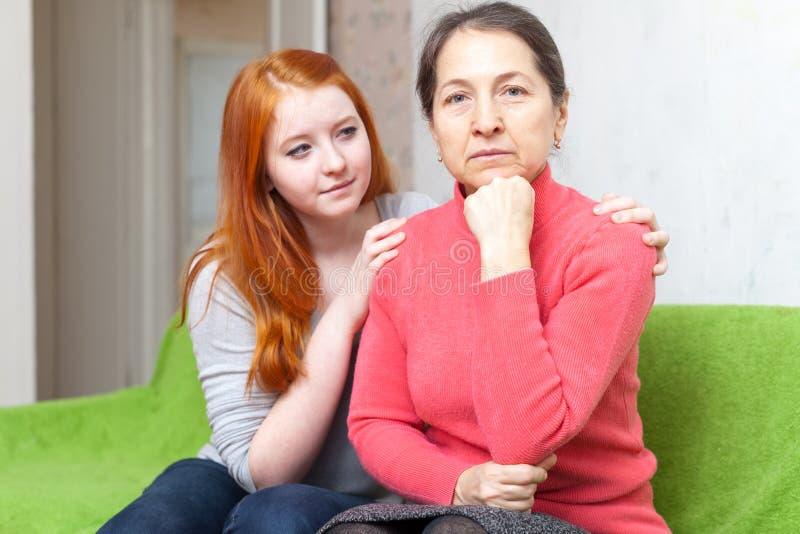 La ragazza teenager chiede il perdono dalla madre immagini stock libere da diritti