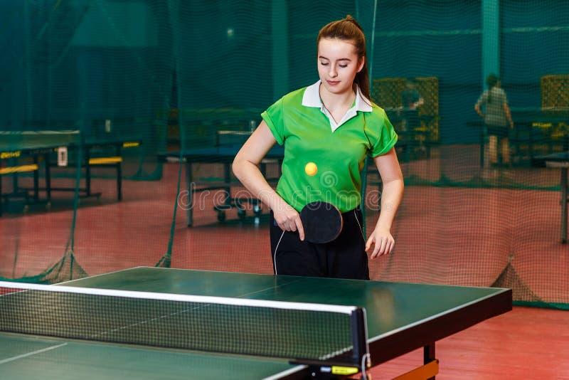 La ragazza teenager di quindici anni gioca la palla nel ping-pong immagine stock