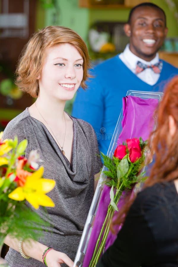 La ragazza teenager nel negozio di fiore compra le rose immagine stock libera da diritti