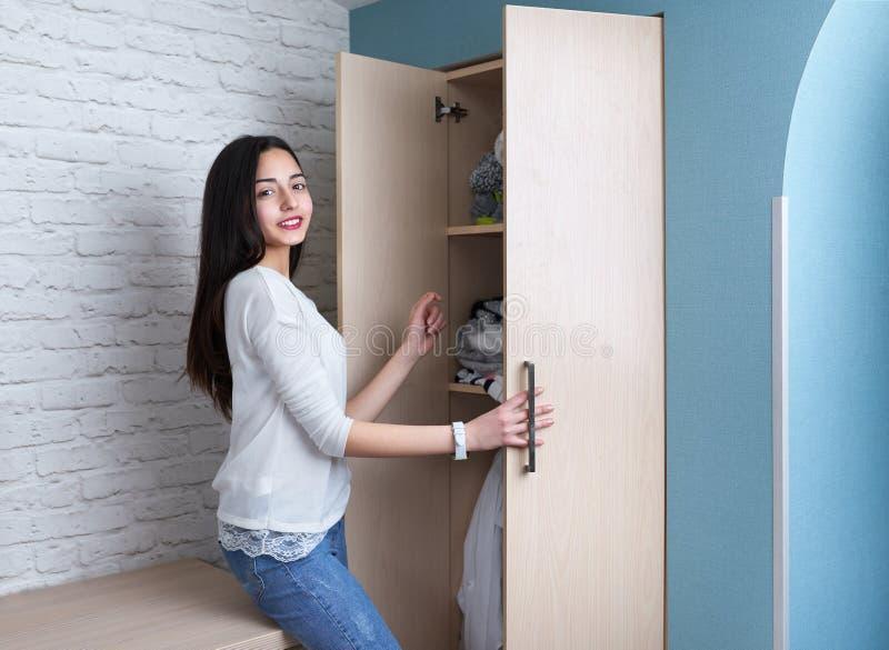 La ragazza teenager ottiene i vestiti dal guardaroba fotografia stock libera da diritti