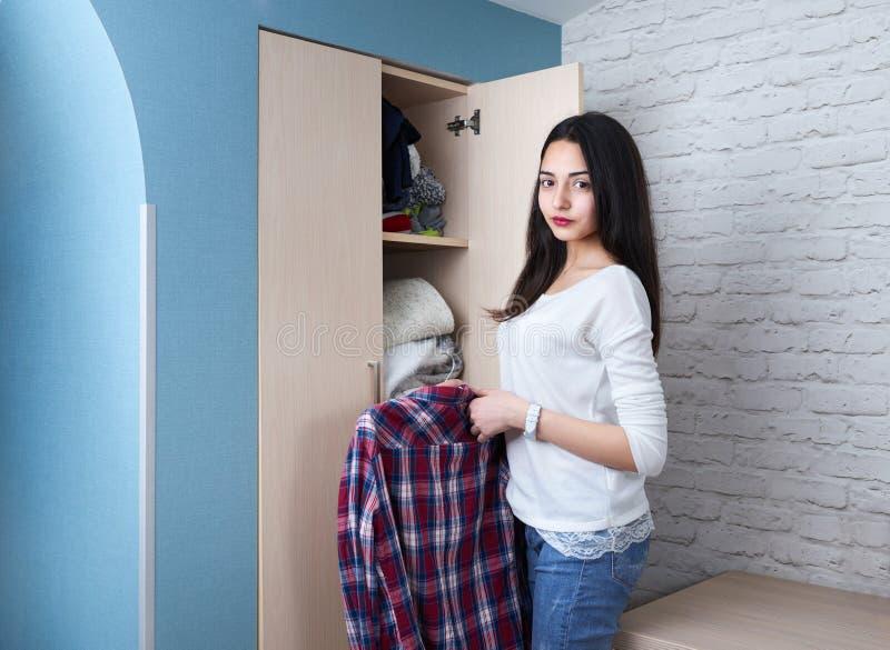 La ragazza teenager ottiene la camicia dal guardaroba immagine stock