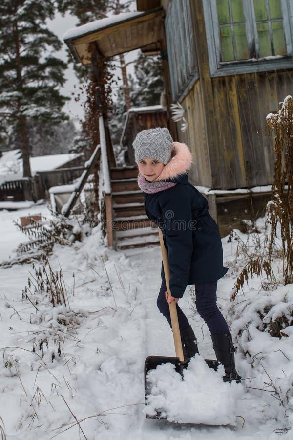 La ragazza teenager pulisce la neve vicino ad una casa rurale Inverno fotografia stock