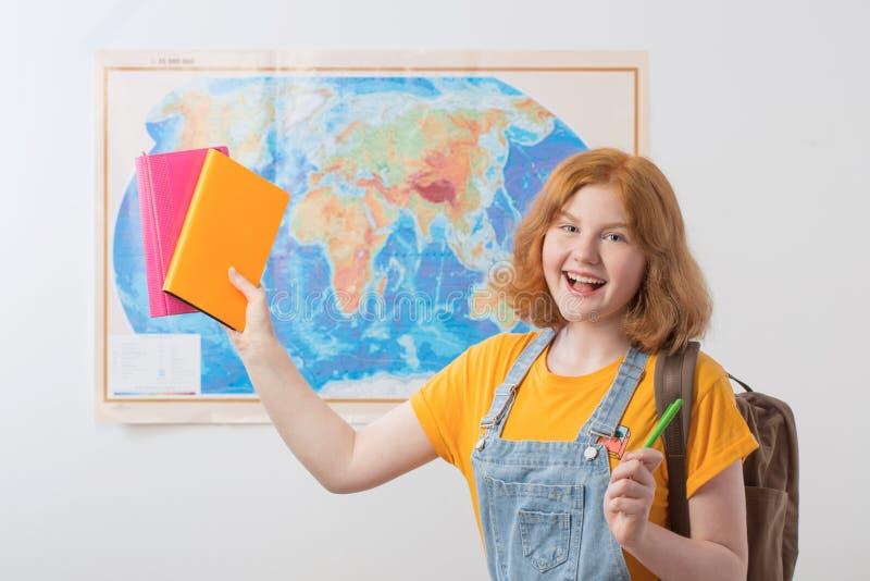 La ragazza teenager sta alla mappa geografica fotografia stock libera da diritti