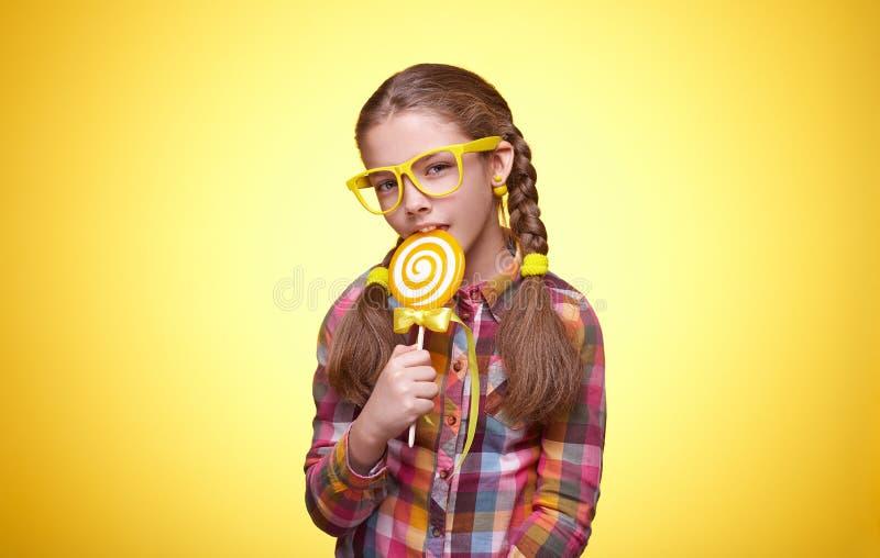 La ragazza teenager sveglia mangia la lecca-lecca su fondo giallo immagini stock libere da diritti