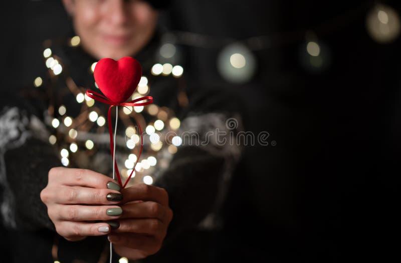 La ragazza tiene il cuore rosso a disposizione su un fondo del bokeh immagini stock