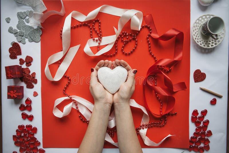 La ragazza tiene il cuore in sue mani su un fondo festivo fotografia stock libera da diritti