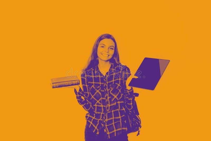 La ragazza tiene il libro e la compressa in sue mani Di nuovo al banco arancio e blu bitonali fotografia stock libera da diritti