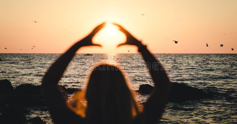 La ragazza tiene il sole vicino al mare al tramonto fotografia stock