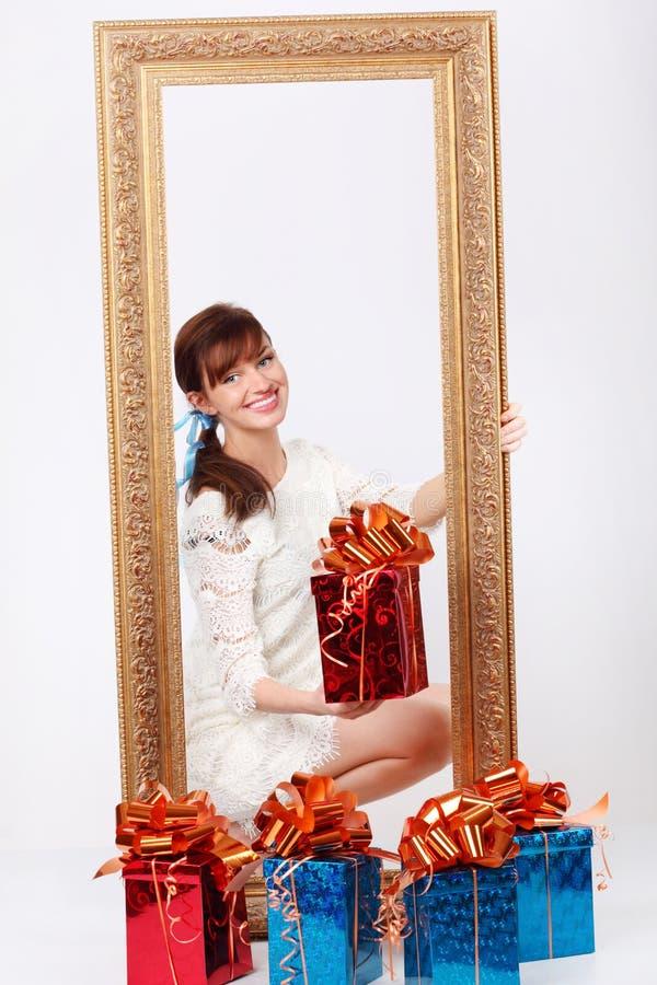 La ragazza tiene la casella con il regalo e guarda fuori dal blocco per grafici immagine stock