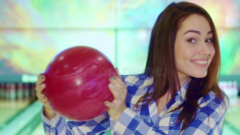 La ragazza tiene la palla da bowling vicino al suo fronte fotografia stock libera da diritti