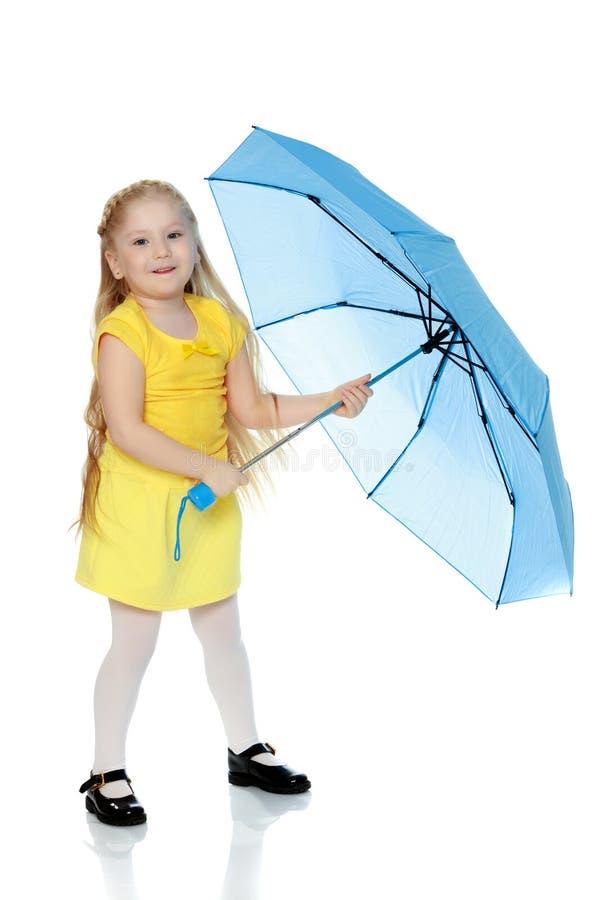 La ragazza tiene un ombrello blu in sue mani fotografia stock libera da diritti