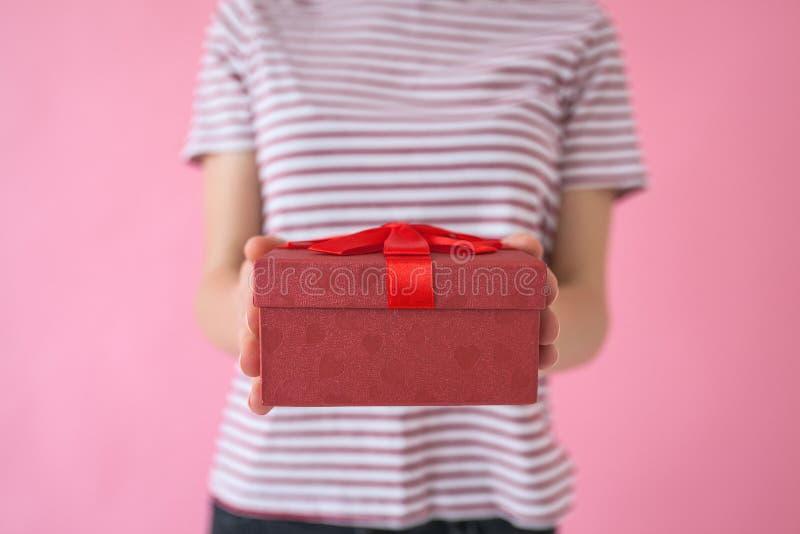 La ragazza tiene un regalo in sue mani immagine stock