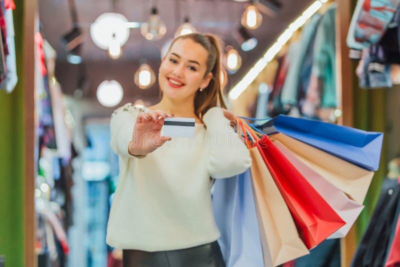 La ragazza tiene una carta di credito ed i sacchetti della spesa con un deposito immagini stock
