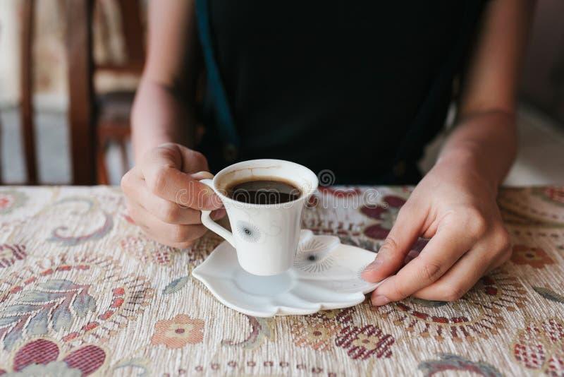 La ragazza tiene una tazza di caffè turco tradizionale aromatico naturale in un caffè della via immagini stock