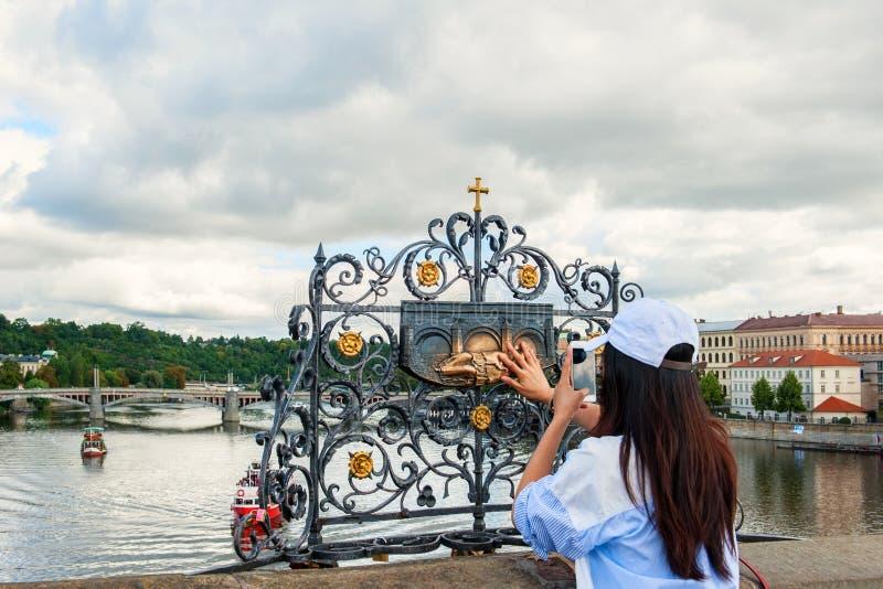 La ragazza tocca la statua della st John Nepomuk sul ponte Praga di Charles Il tocco di persona alla placca commemorativa del Sai immagine stock