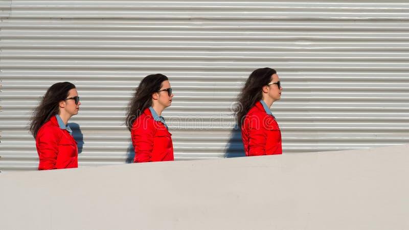 La ragazza tripla cammina fra una parete e uno strato fotografie stock