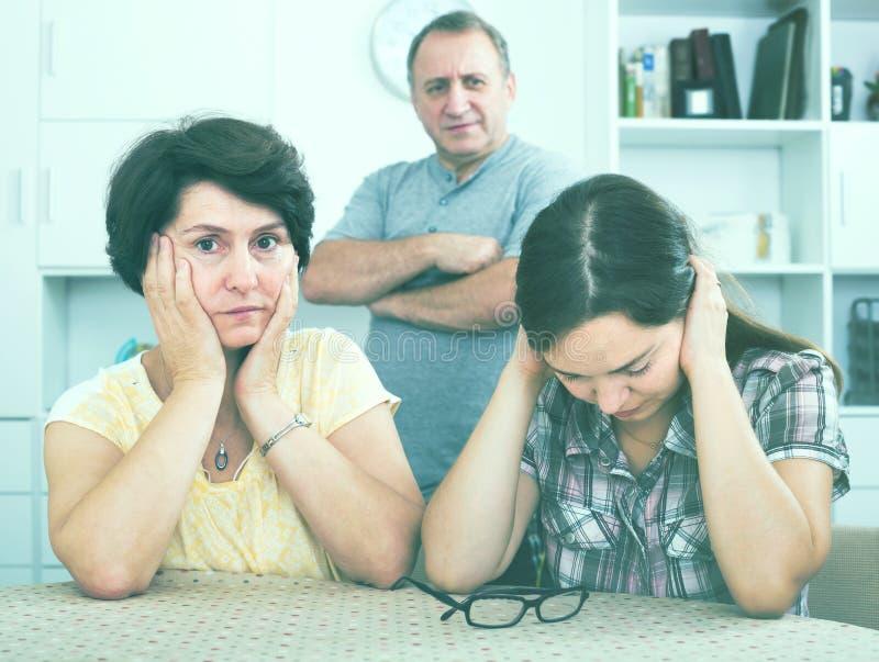 La ragazza triste è infastidita dai suoi genitori del pensionato fotografia stock