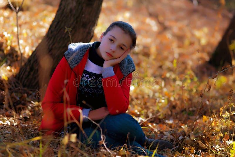 La ragazza triste si siede su un'erba di autunno fotografie stock libere da diritti