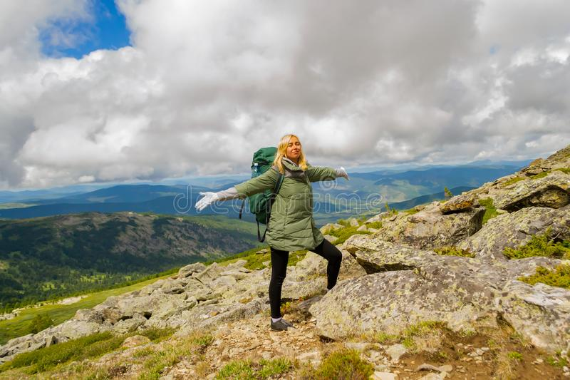 La ragazza turistica bionda in un rivestimento verde e con uno sta dello zaino fotografia stock libera da diritti