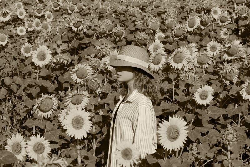 La ragazza in un cappello di paglia sta stando in un grande campo dei girasoli Giovani adulti fotografie stock libere da diritti
