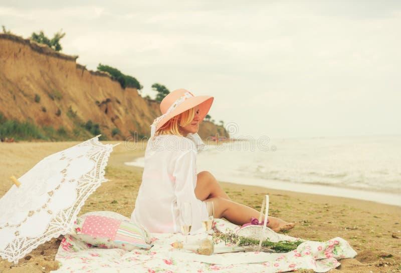 La ragazza in un cappello rosa si siede sulla spiaggia su una spiaggia selvaggia Picnic di estate sulla spiaggia immagini stock