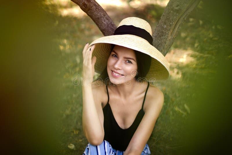 la ragazza in un cappello sotto un albero sta riposando, vita felice fotografia stock