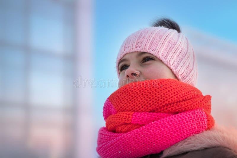 La ragazza in un cappello tricottato con un bub e un cappuccio lanuginoso guarda avanti fotografia stock