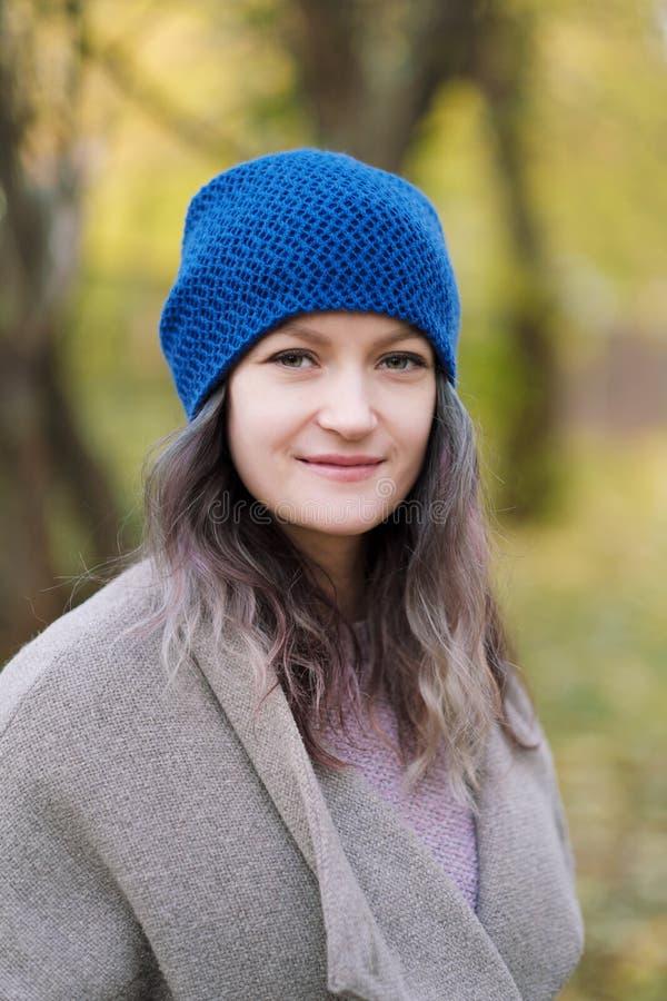 La ragazza in un cappotto ed in un cappello blu su un fondo degli alberi e delle foglie di acero di autunno immagini stock