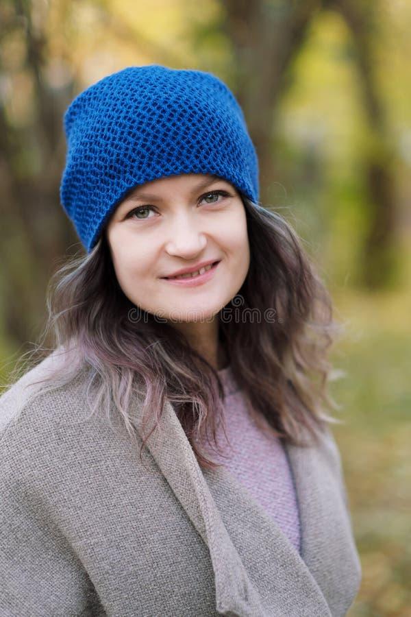 La ragazza in un cappotto ed in un cappello blu su un fondo degli alberi e delle foglie di acero di autunno immagini stock libere da diritti