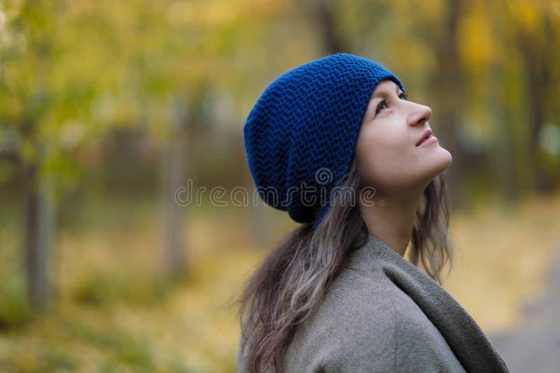 La ragazza in un cappotto ed in un cappello blu su un fondo degli alberi e delle foglie di acero di autunno immagine stock