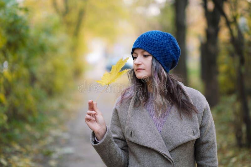La ragazza in un cappotto ed in un cappello blu su un fondo degli alberi e delle foglie di acero di autunno immagine stock libera da diritti