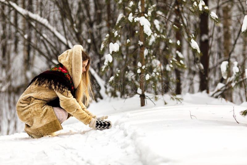 la ragazza in un cappotto leggero con una sciarpa russa sulle sue spalle gioca nella neve sulla via nel parco fotografia stock