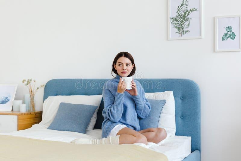 La ragazza in un maglione blu nello stile interno di Hygge con una tazza a disposizione si siede sul letto fotografia stock libera da diritti